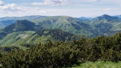 Rakytov - výhled z vrcholu na nejvyšší část hřebene Velké Fatry: úplně vlevo vzadu Krížna, uprostřed mohutná Ploská a vpravo Borišov s červenou střechou chaty pod Borišovom na jeho úpatí. Více vpředu skalnatý Čierny kameň a ještě blíže Minčol.