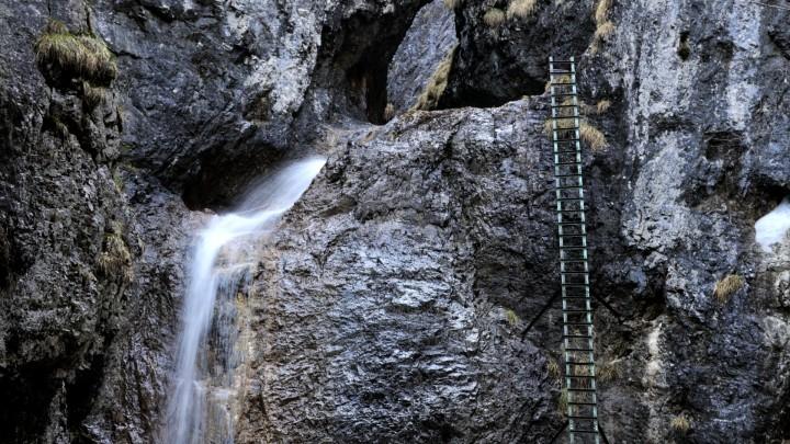 Žebřík podél Velkého vodopádu ústí do úzké skalní soutěsky plné dřevěných lávek