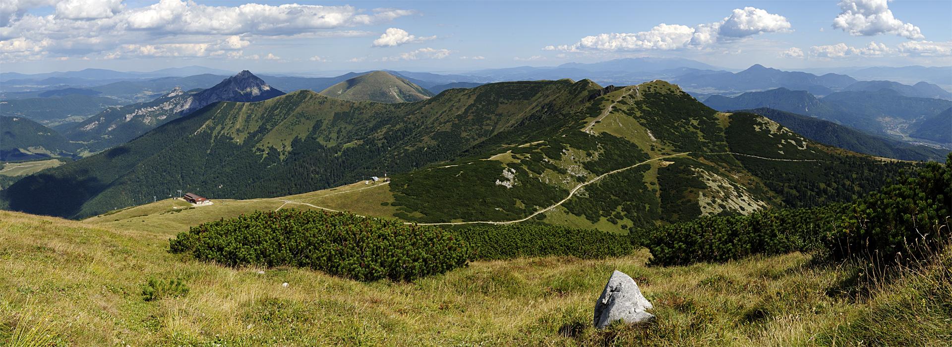 Výhled z Velkého Kriváně na horní stanici lanovky a vrcholy Malý a Velký Rozsutec, Stoh, Poludňový grúň a Chleb. Cesta protínající svah Chlebu vede k chatě pod Chlebom.