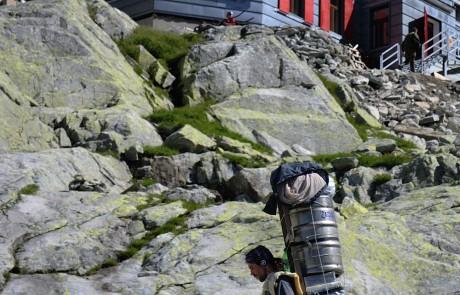 Nosič s těžkou vynáškou odpočívá kousek před chatou pod Rysmi